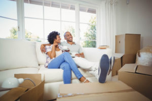 Man & Woman Couple Sitting on Couch with Move-In Boxes Around Them - Gary's Vacuflo Reason for Central Vacuum in New Construction