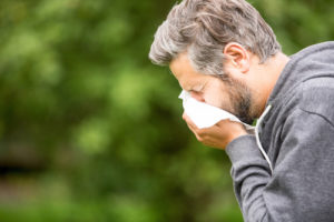 Man Sneezing in Tissue - Gary's Vacuflo Reduces Seasonal Allergies