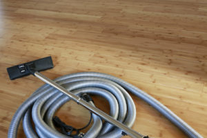 Rolled Up Vacuum and Tube on Hardwood Floor - Gary's Vacuflo Maintenance for Central Vaccum System